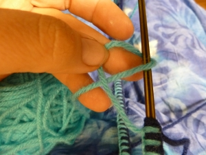 pass you yarn over the hanger and through the loop